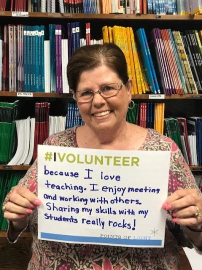 "Literacy Services Volunteer holding ""Why I Volunteer Sign""."